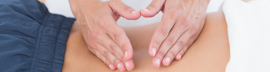 Frau erhält physiotherapeutische Anwendung im Rückenbereich.